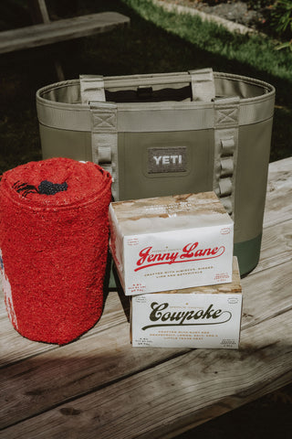 picnic blanket sitting next to a yeti cooler and two cartons of big country sparklin cocktails