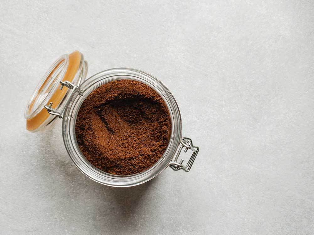 Harvested organic cocoa powder in a glass jar on the counter