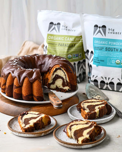 A sour cream pound cake recipe sitting on a platter beside smaller plates of cake, big country organic cane sugar, and big country organic powdered sugar