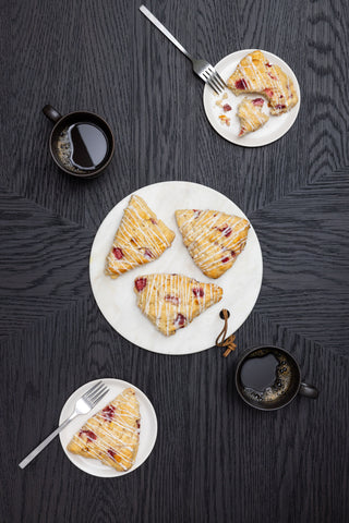 strawberry scones on white plates next to cups of coffee on dark background