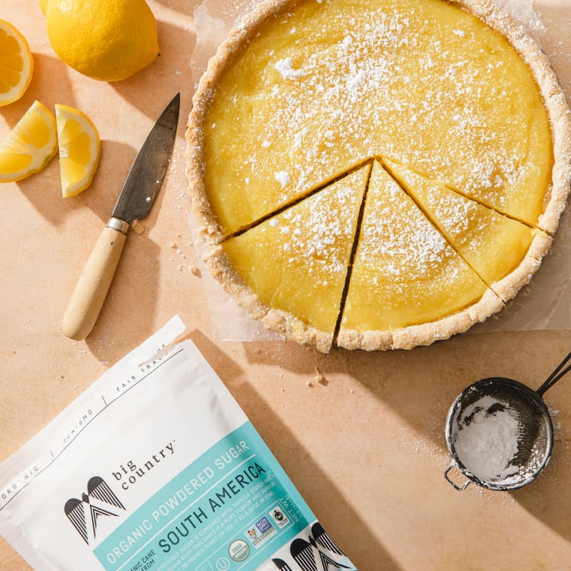 A gluten-free vegan lemon tart cut into slices sitting beside Big Country organic powdered sugar, lemons, a knife, and a measuring cup