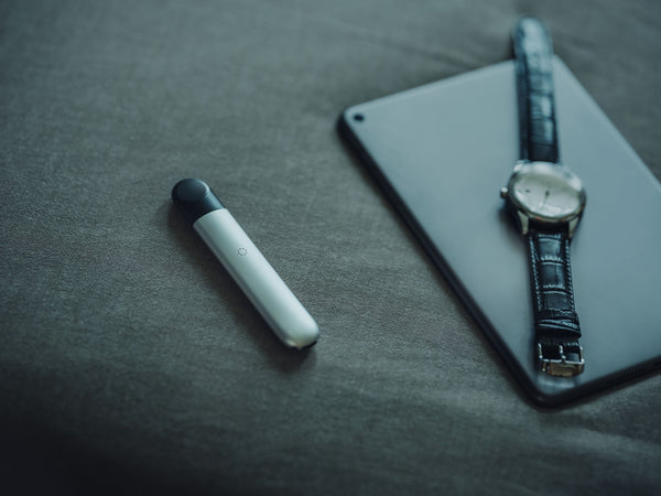 A RELX vape device displayed alongside a mobile phone and a watch