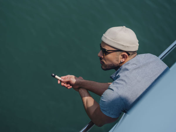 A man looking out into the sea while standing on a boat and holding a RELX vape device.