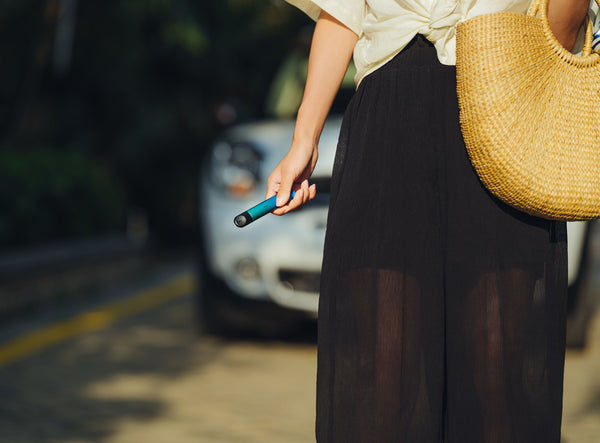 A woman in casual wear holding a blue RELX vape device in her right hand as she walks down a street.