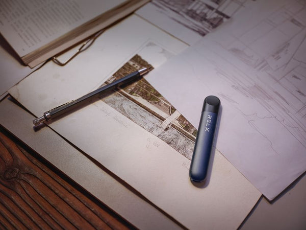 RELX vape device displayed alongside a pencil on a documents and books