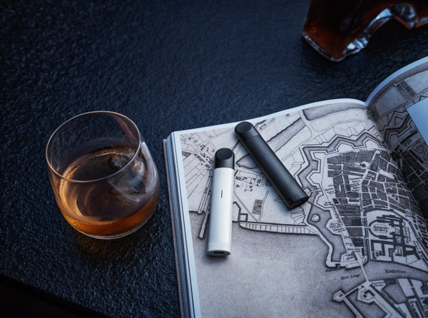 Two vapes on the opened magazine with a glass of tea