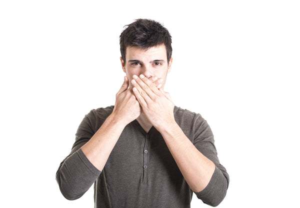 A man covers his mouth with his hands.