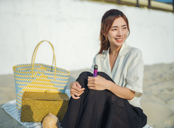A smiling woman sitting on a mat as she holds a RELX vape device in her left hand.