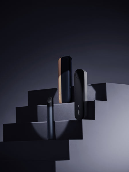 RELX Infinity device and Infinity Charging Cases standing on steps.
