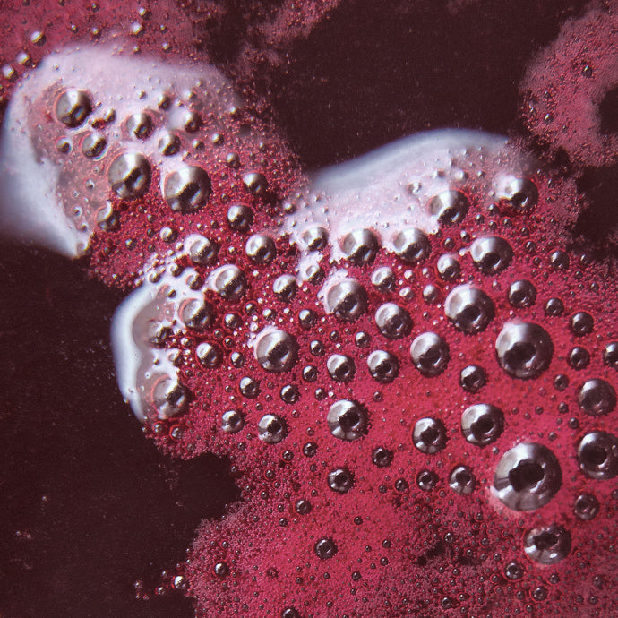 Bubbles on surface of maroon liquid