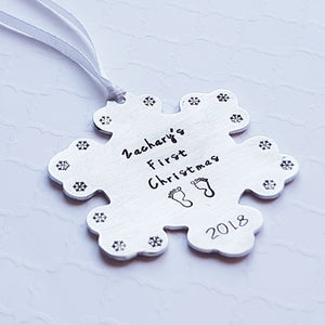 """baby's first christmas"" snowflake-shaped christmas ornament with baby's name, birth year, and tiny footprint stamps"