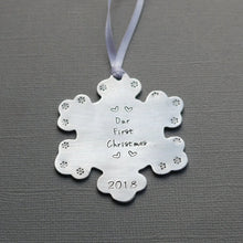 "Load image into Gallery viewer, ""our first christmas"" snowflake-shaped christmas ornament with tiny hearts and year"