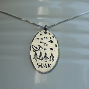 Silver pendant with birds soaring over a forest
