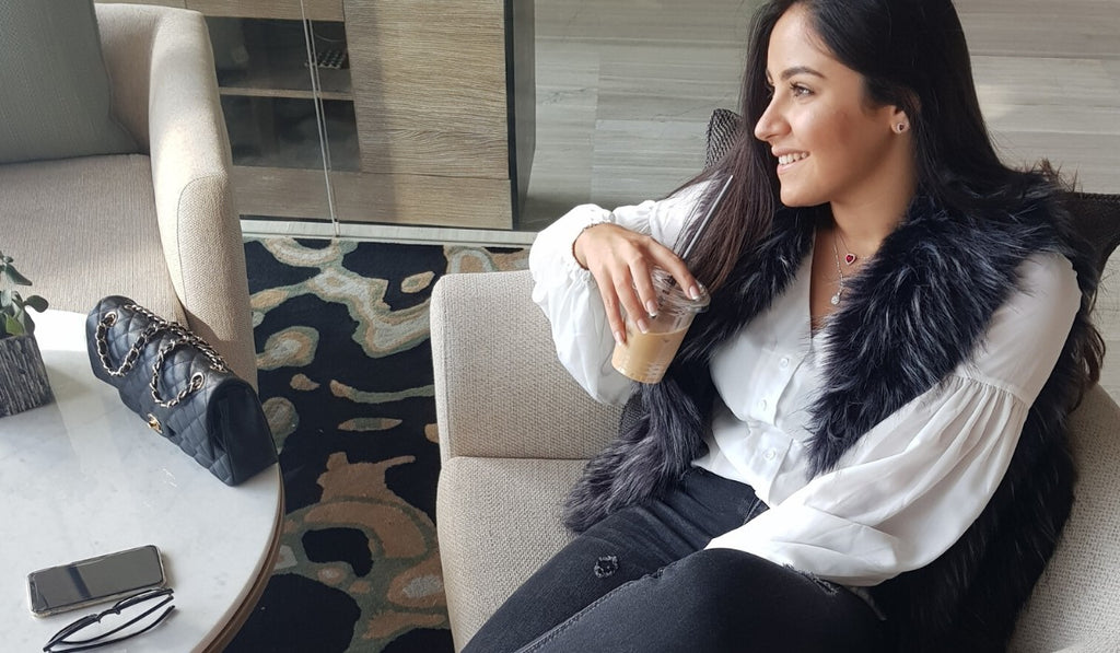 beautiful girl sitting and drinking coffee in her monaco black faux fur vest