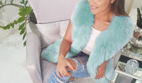 fashionable lady sitting in chair wearing ripped jeans and an amsterdam mint faux fur vest