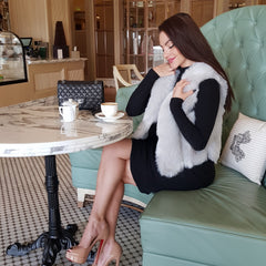 pretty girl sitting having coffee in a black dress and a Furever paris grey faux fur vest