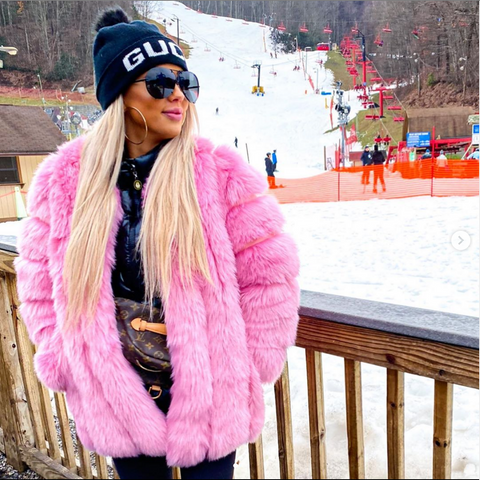 girl standing in snow wearing a Furever moscow pink faux fur coat