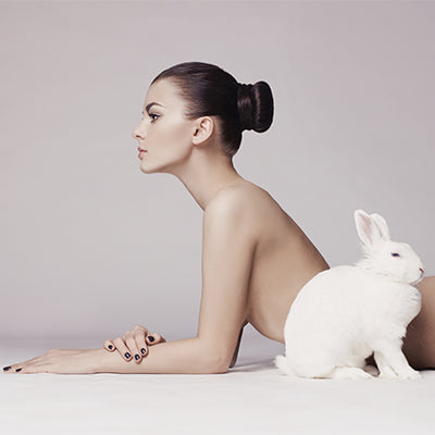 beautiful naked woman laying next to a white bunny