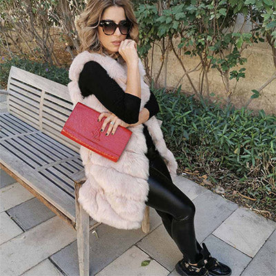 pretty woman wearing sunglasses and sitting on a bench wearing a furever london beige faux fur vest