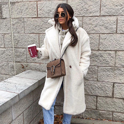 girl standing outside holding a coffee wearing a furever prague ivory faux fur teddy coat