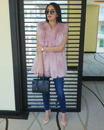 chic woman standing in sunglasses wearing an amsterdam pink faux fur vest