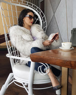 chic woman sitting at a table on her phone wearing a chicago raccoon white faux fur coat