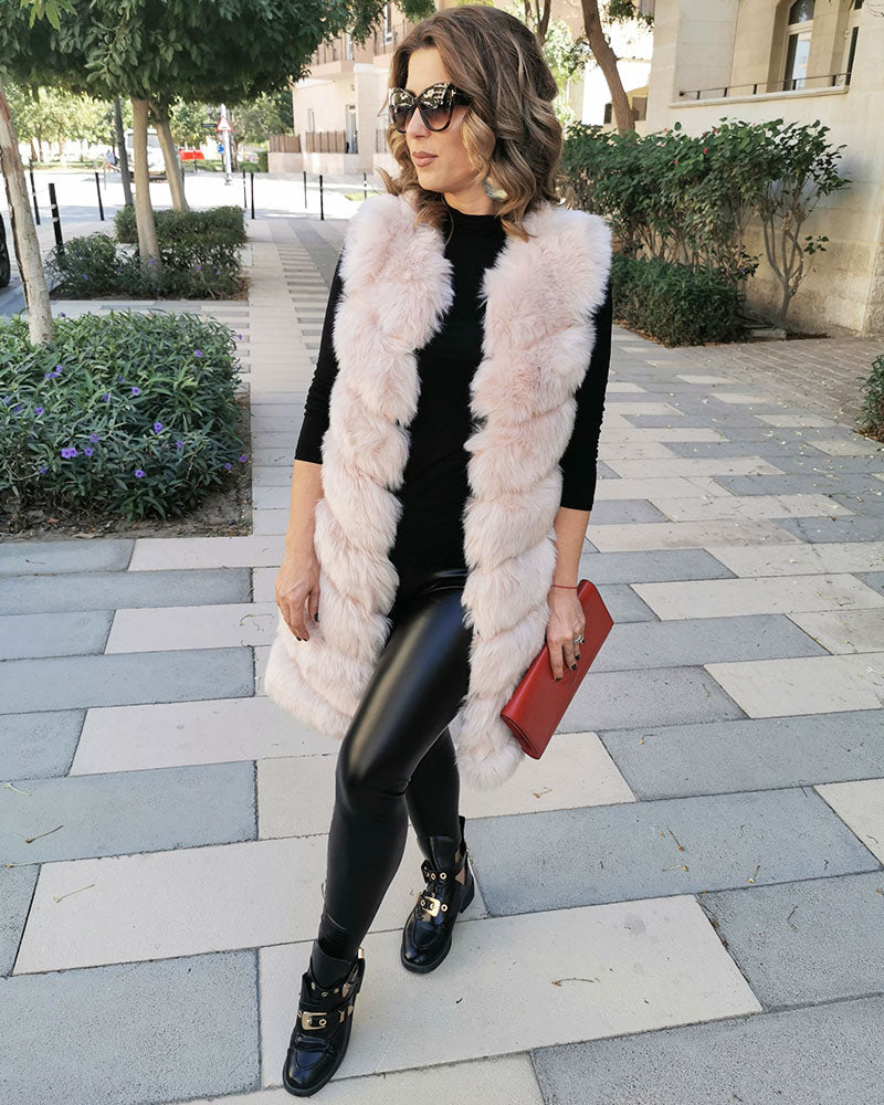 classy woman standing in a park wearing all black and a london beige faux fur vest