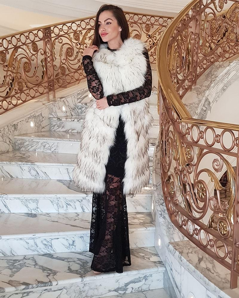 stunning model on marble staircase wearing a long black dress and a london raccoon white faux fur vest