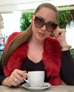 stylish young lady drinking coffee and wearing a new york red faux fur vest