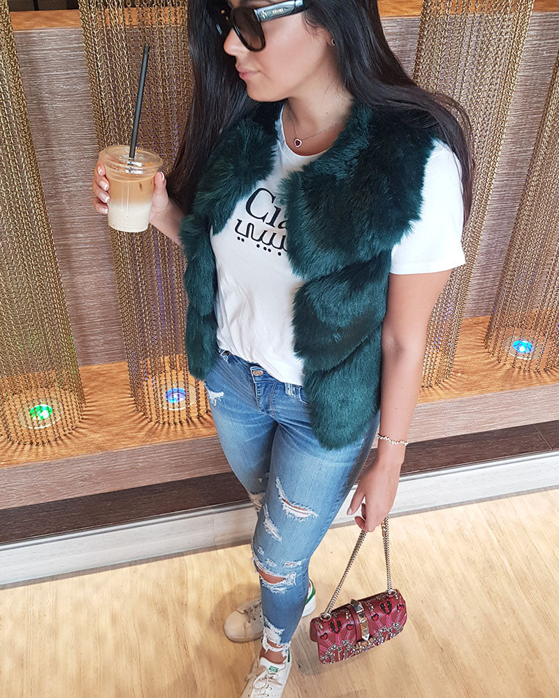 stylish girl holding coffee wearing a new york green faux fur vest | furever faux fur