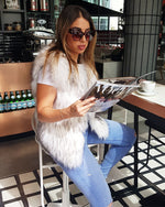 fashionable girl sitting in a chair reading a magazine and wearing a new york raccoon white faux fur vest