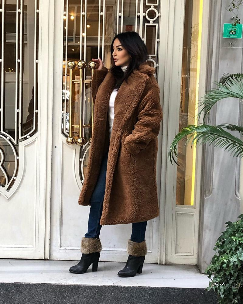 beautiful model standing at a door wearing a prague brown faux fur teddy coat