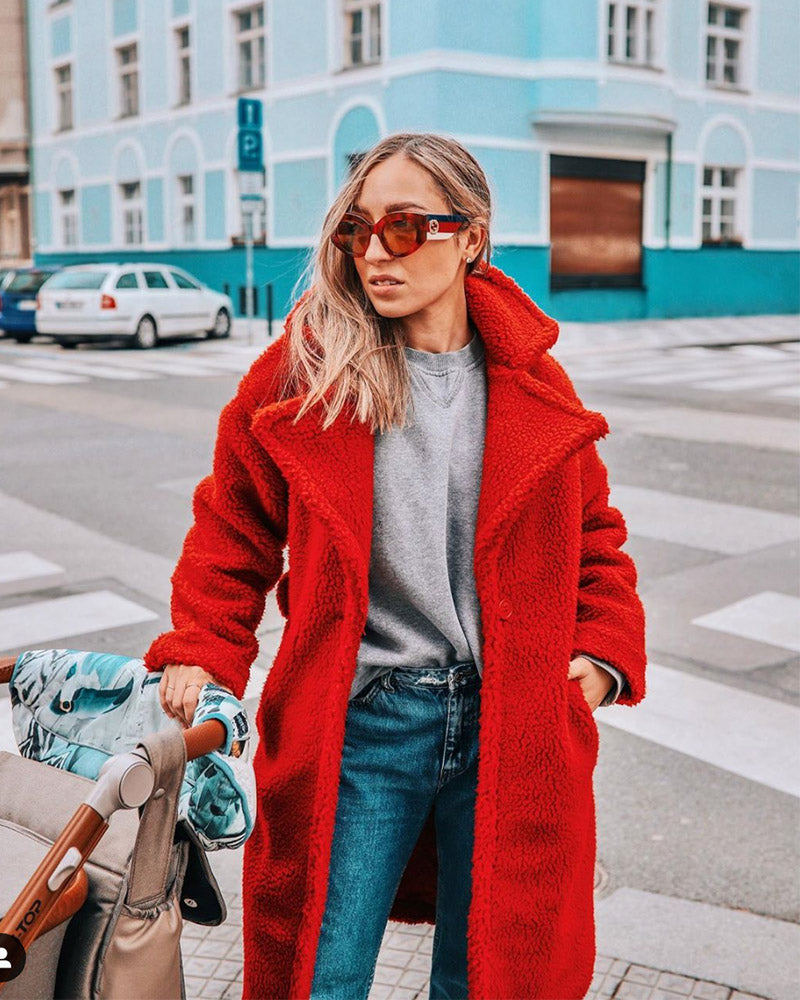 fashionable woman with a stroller wearing sunglasses and a prague red oversized faux fur teddy coat