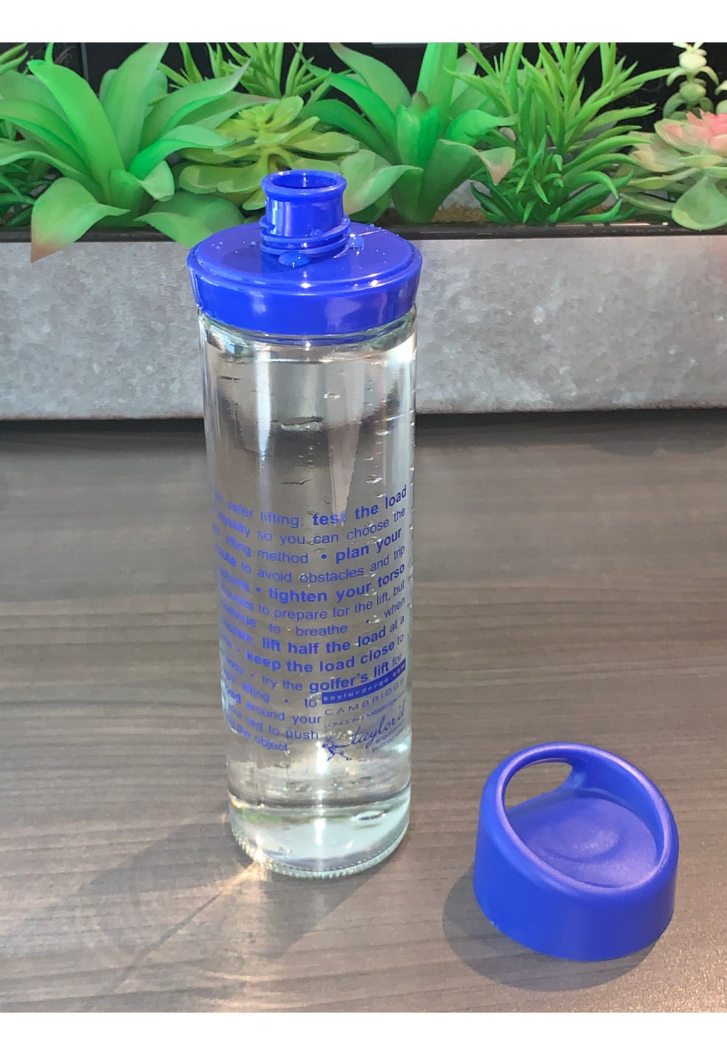 photograph of glass water bottle with blue lid and spout, showing ergonomics lifting tips imprint
