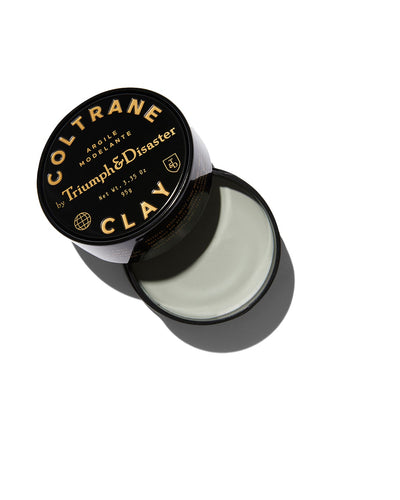 Opened black jar of Triumph & Disaster Coltrane Clay hair product on white background