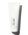 The Grey Exfoliating Face Scrub in white tube on white background