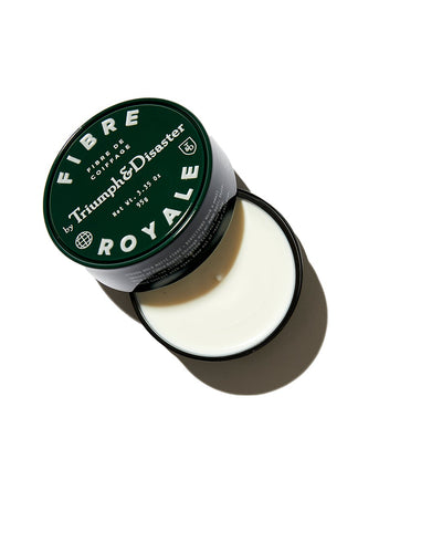 Opened Triumph & Disaster Fibre Royale hair product in black jar on white background