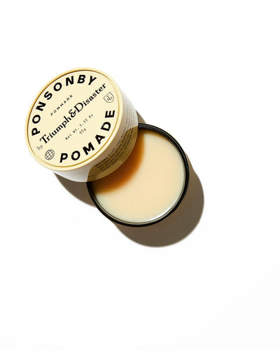 Opened Triumph & Disaster Ponsonby Pomade hair product in cream coloured jar with black text on white background