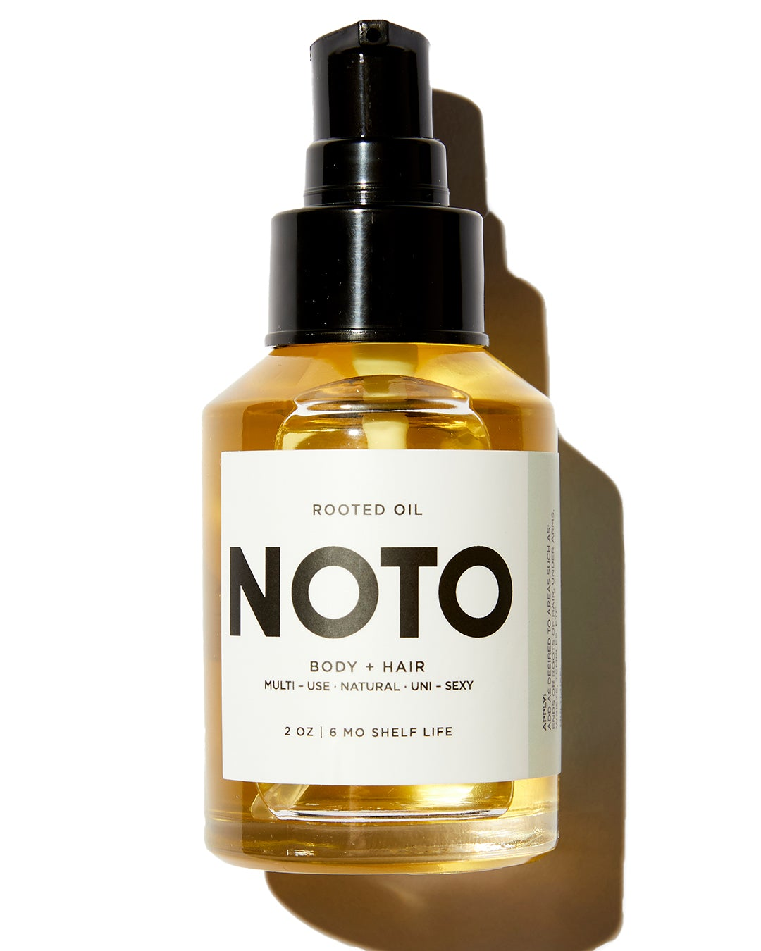 NOTO Rooted oil in clear oil dropper bottle with white label and black lid on white background