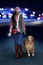 Load image into Gallery viewer, Day and night dog walking bag. Pictured is a lady with the walking bag walking a golden retriever at night to show the reflective straps and flashlight.