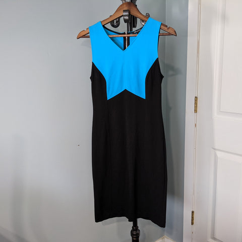 This is a beautiful blue and white dress made by Kenneth Cole. The shoulders and chest are a beautiful blue while the body down to the hem is black. The dress is hanging on a dark wood hanger on a black coat rack.