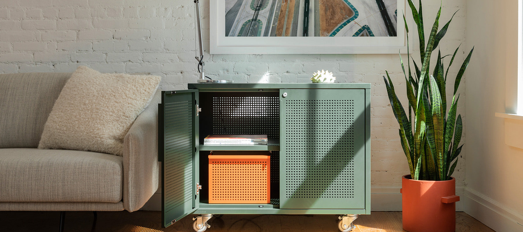 Heartwork Active Duty Assistant in deep green with open door and a warm orange basket inside in home setting
