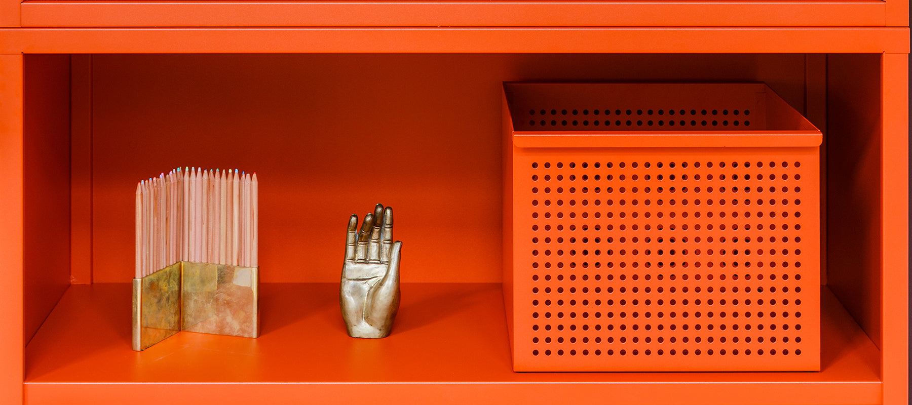 Heartwork Perforated Basket in warm orange on a shelf with objects