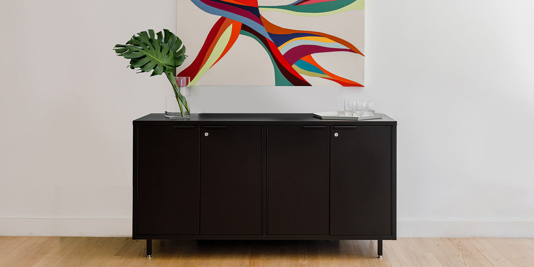 Heartwork Active Duty storage credenza in black against white wall with a painting in the background