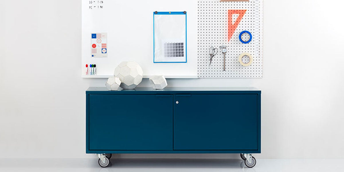 Heartwork storage credenza in blue against a white wall in a staged setting