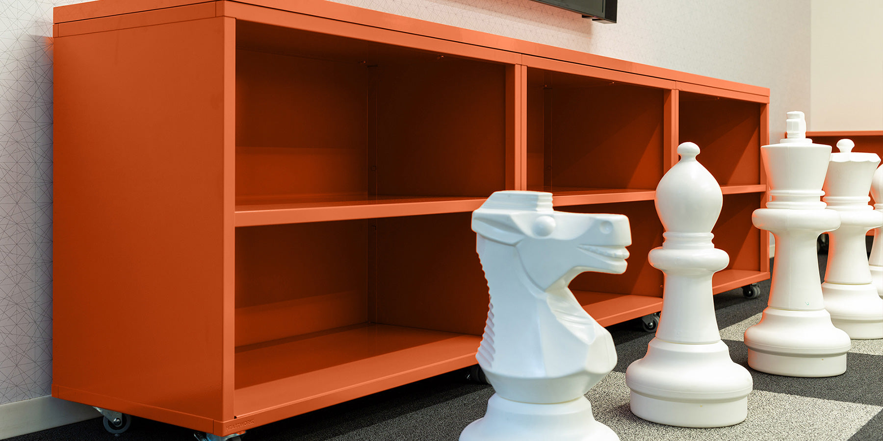 Heartwork Building Block bookcase in warm orange staged with giant white chess pieces