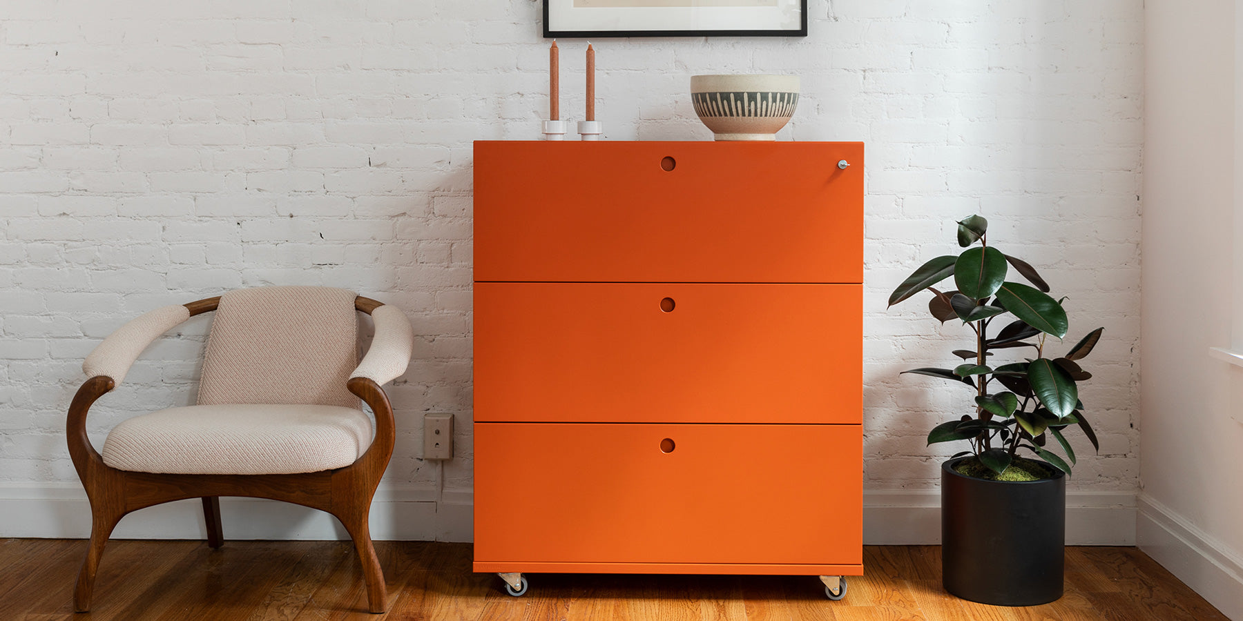 Heartwork Building Block lateral file with three drawers in orange in home setting next to an armchair