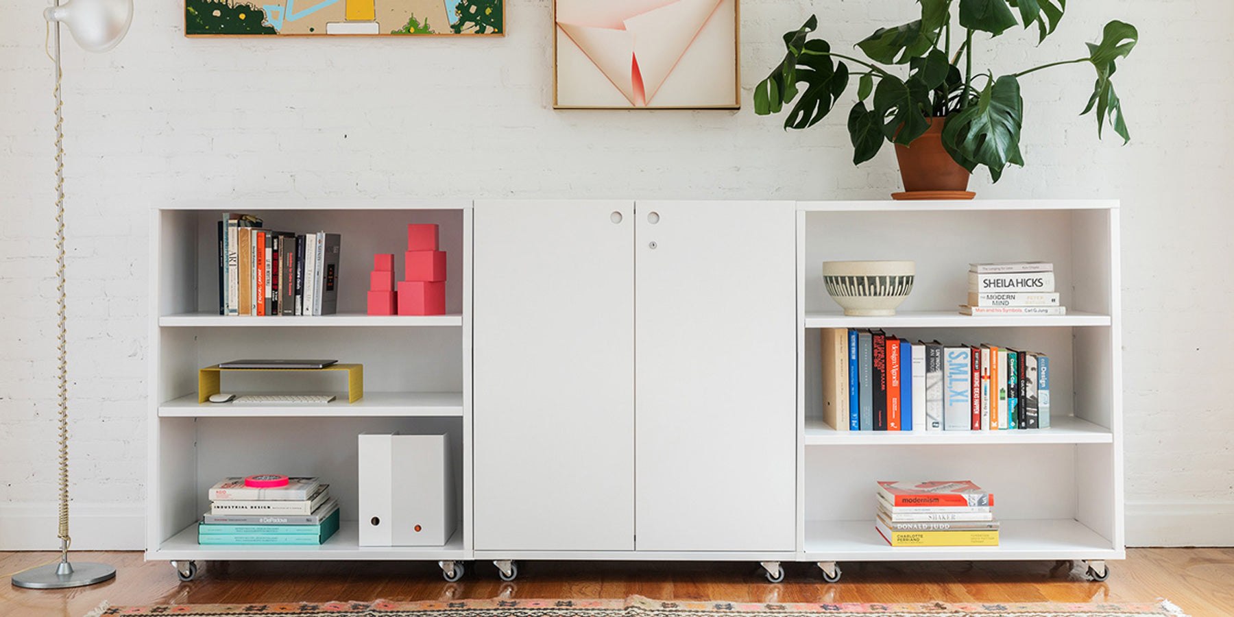 Heartwork Building Block storage cabinet in white in home setting between two bookcases