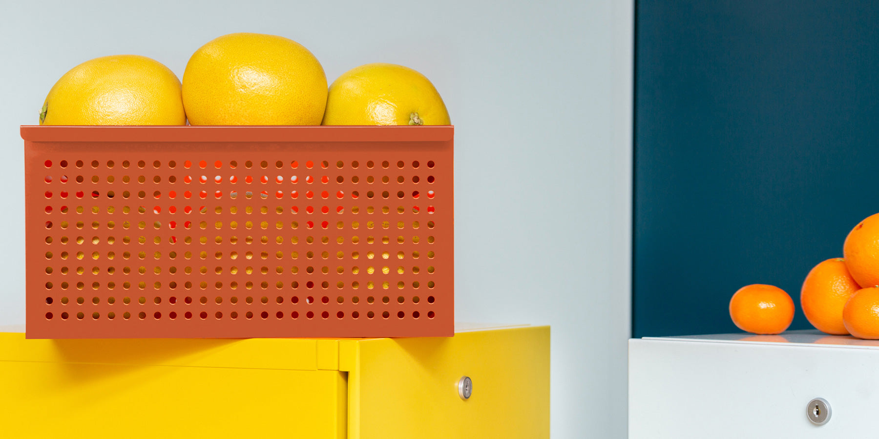 Heartwork perforated basket in orange staged with lemons