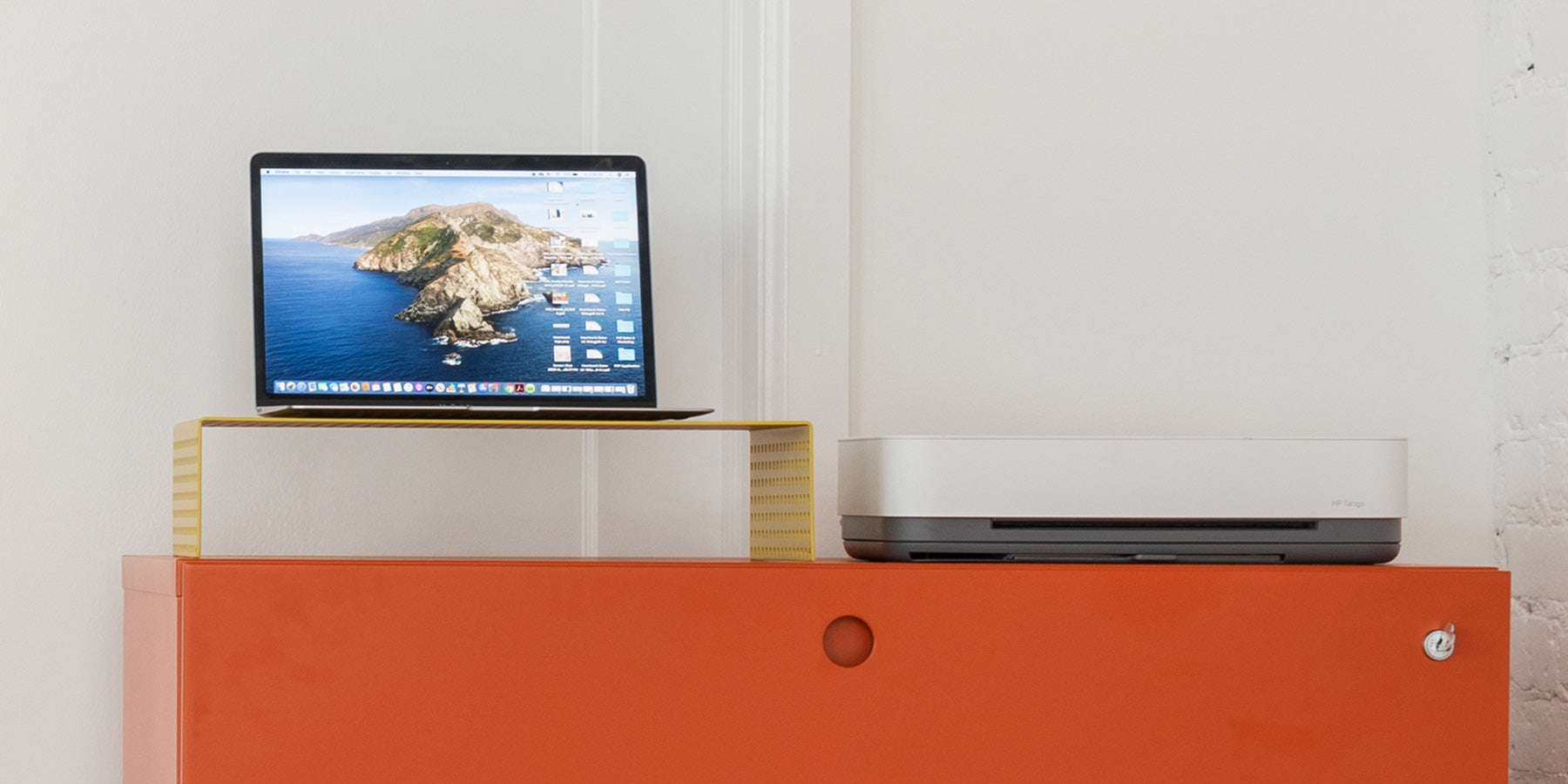 Heartwork Monitor Stand in yellow on top of orange Lateral File cabinet with laptop and printer